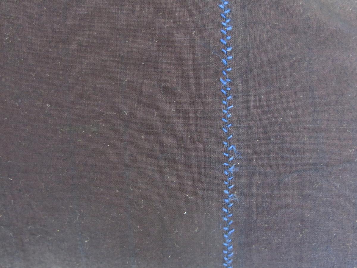 detail: over de naad van het schort werd met de hand een sierrand geborduurd