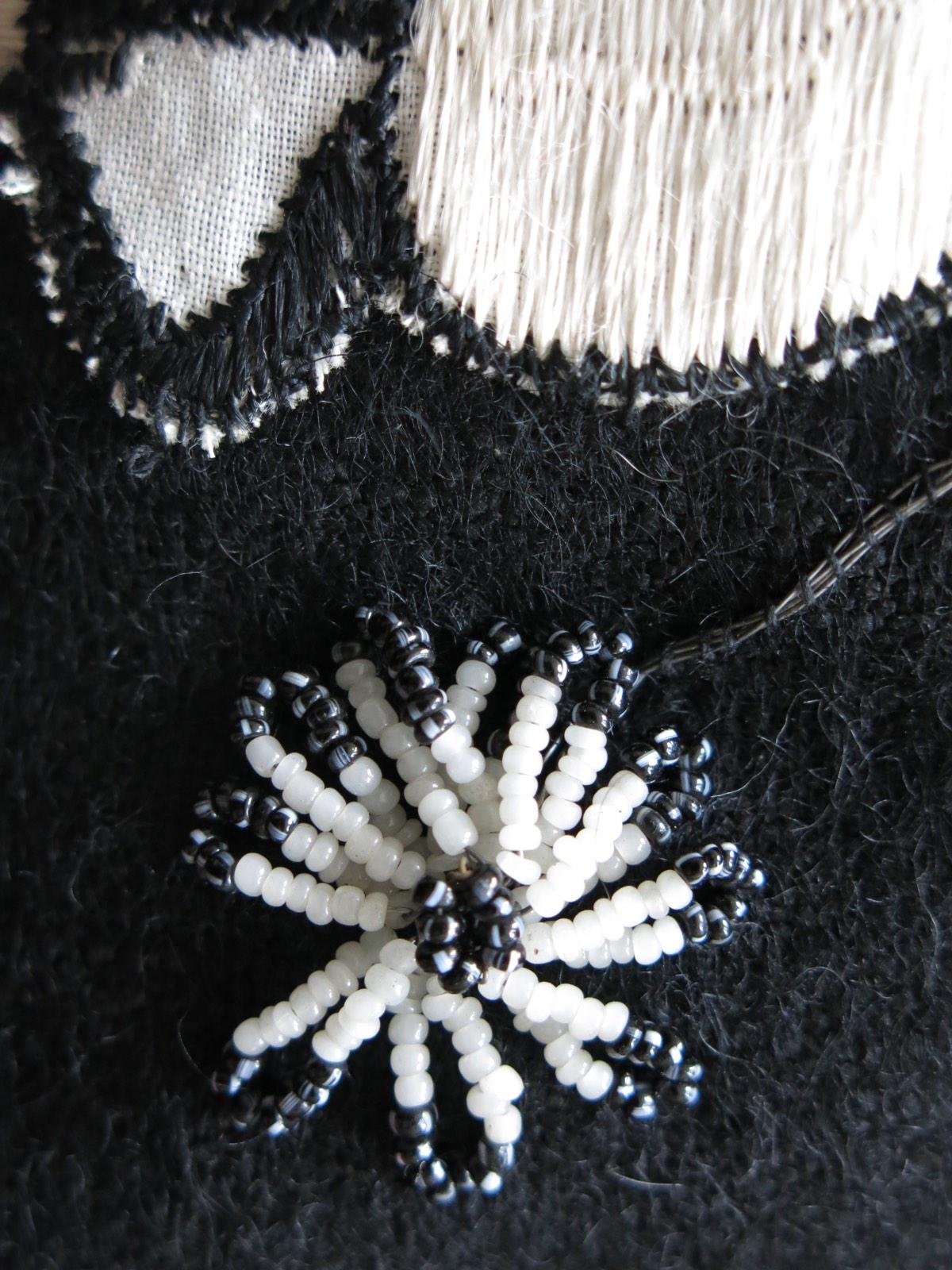 detail: glaskraaltjes op ijzerdraad tot bloemetje geregen, gekleurde kraaltjes werden geverfd