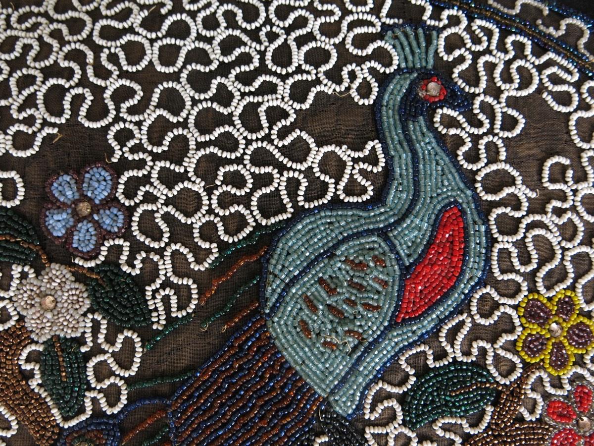 detail: pauw, een veel voorkomende vogel in India:rode kraaltjes waren erg duur want er moest goud bij het verfbad