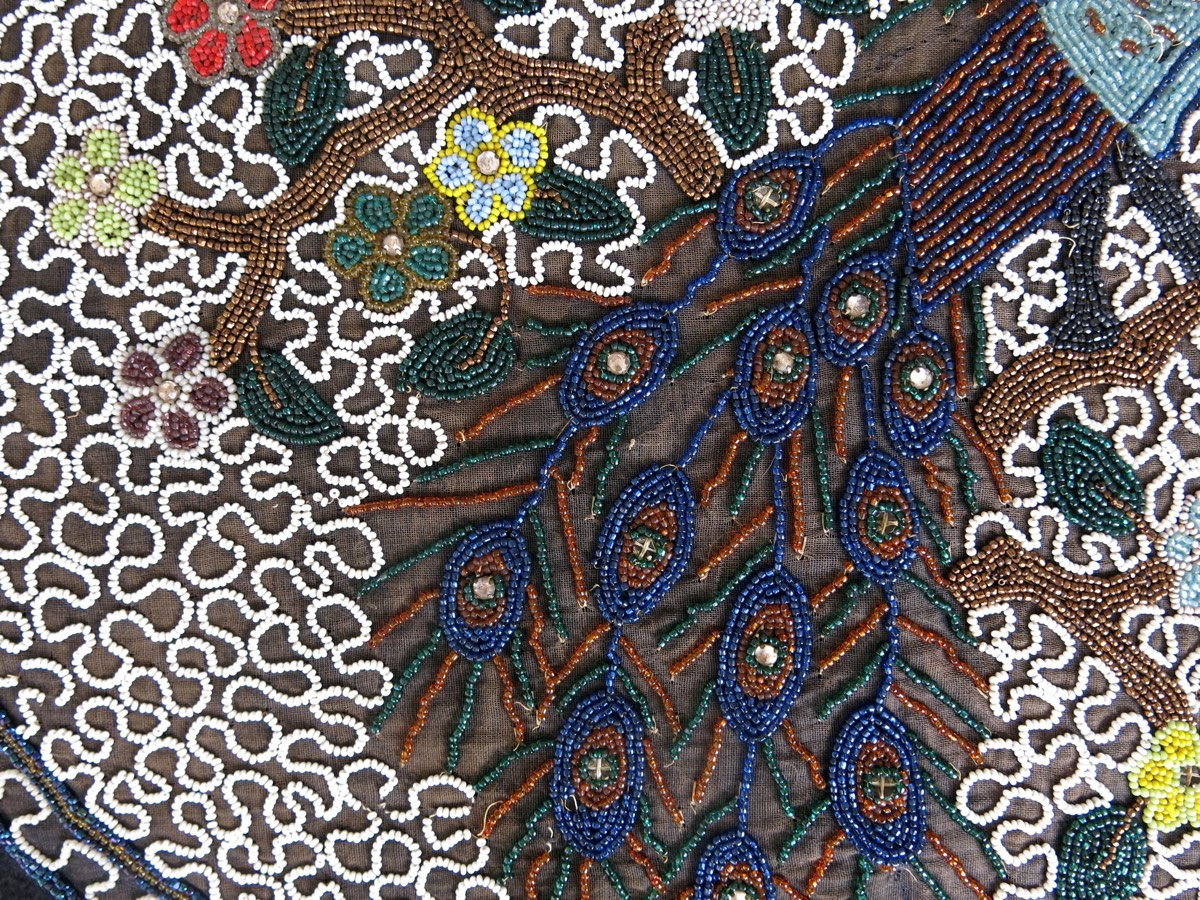 detail: witte opalinekraaltjes worden door en door gekleurd met natuurlijk verfstoffen, voor de rode kleur gebruikte men goud dus die waren erg duur