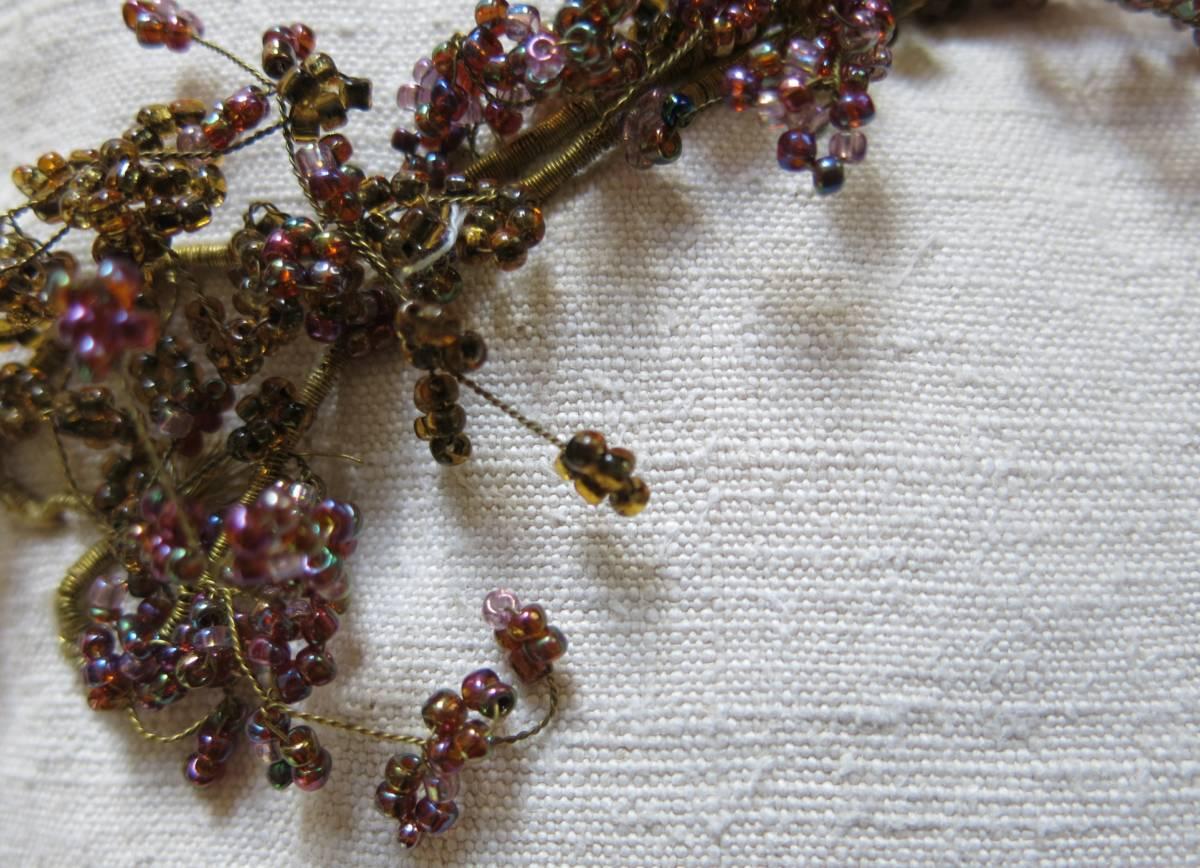 detail: takje met koper-/gouddraad omwikkeld, de oude paarse en okerkleurige glaskraaltjes worden op messing-draad geregen ±1910