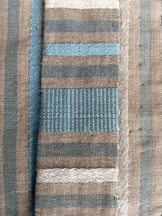 detail: overslag van greinen keus haaks op de draad; grein is een mengweefsel, een linnen schering en een wollen inslag (soms geitenhaar of kameelhaar)