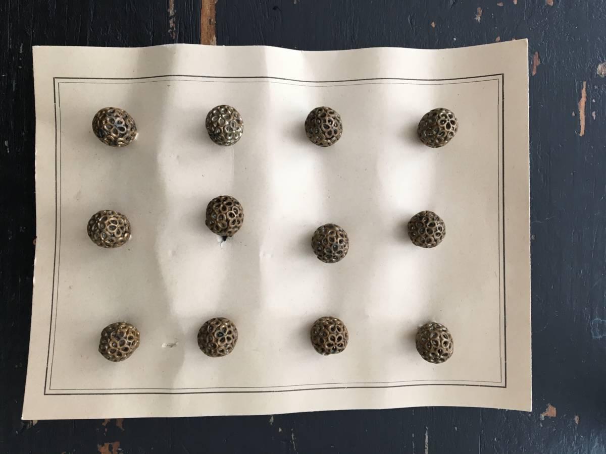 detail: vuurvergulde geperforeerde bolvormige knopen ±1920; de knoop werd gedoopt in een legering van kwik en goud en in vuur gedroogd; nu een verboden methode